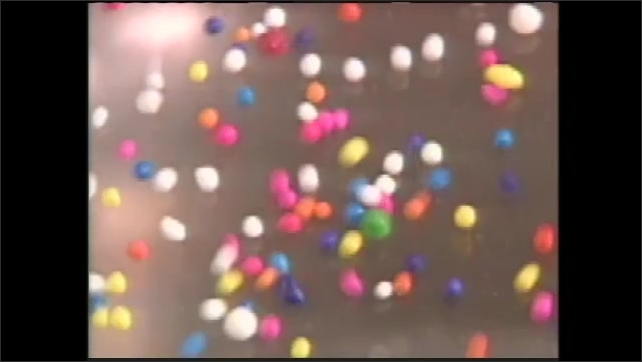 1990s: hand bangs wooden spoon against metal baking sheet as sprinkles bounce on homemade drum nearby, bouncing candy sprinkles