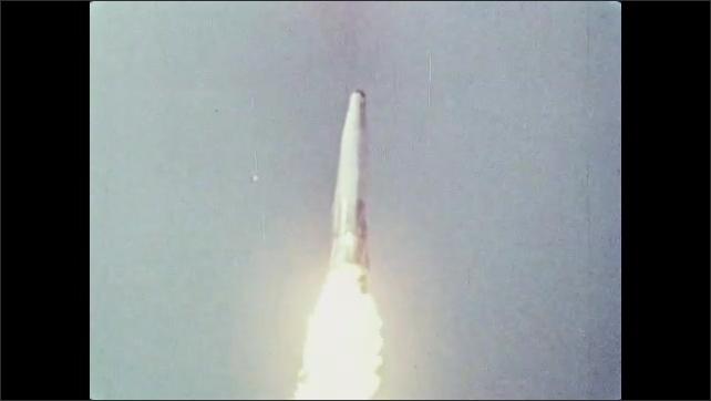 1960s: Rocket flies into sky.  Pieces of rocket fall off.