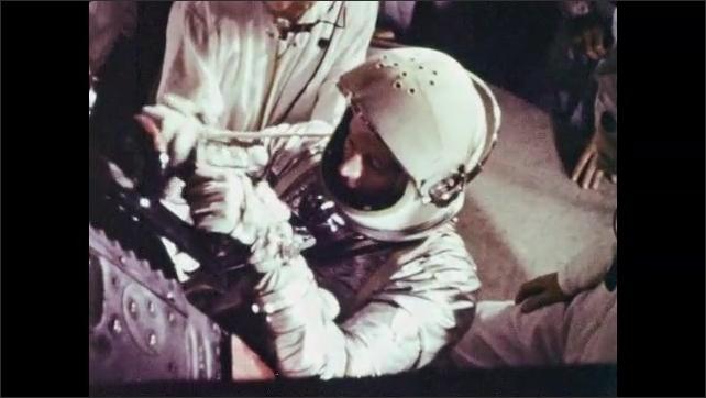 1960s: Astronaut gets in the spacecraft, two men help him to get in.