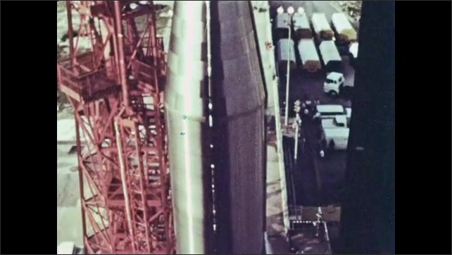 1960s: Man fastens the spacecraft door while another man holds it. Mercury-Atlas 9 space rocket at the launch pad. The top of the rocket at the launch pad.