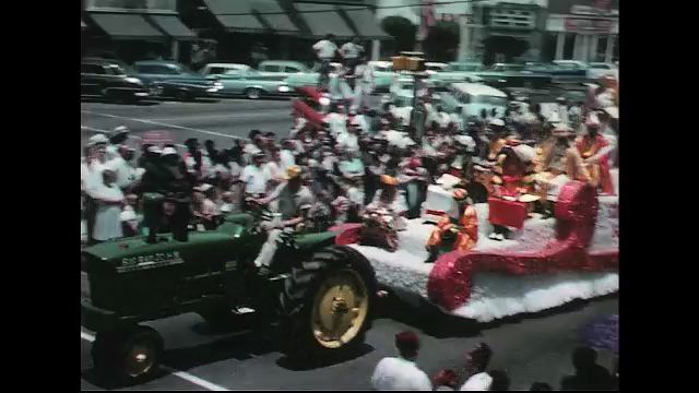 UNITED STATES 1960s: Tractor pulls Shriner float in parade, Shriners on fire engine / Shriners march in parade.