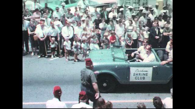 UNITED STATES 1960s: 'Durham Shrine Club' car in parade, Shriner gets into car / Views of Shriners in other cars with 'Durham Shrine Club' banners / Car with 'Elizabeth City Shrine Club' banner.
