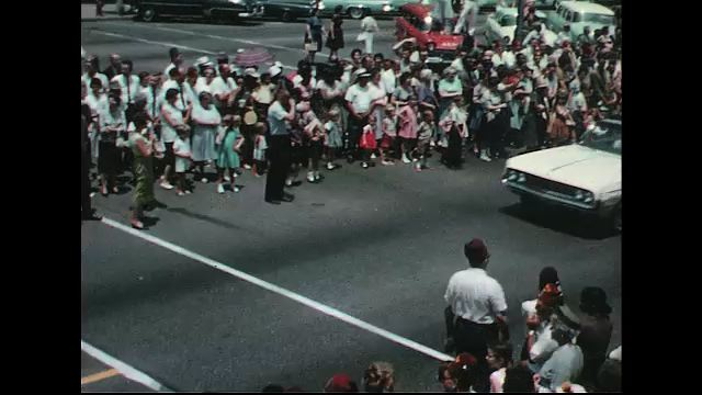 UNITED STATES 1960s: Two convertibles carrying Shriners in parade / Convertible speeds up.