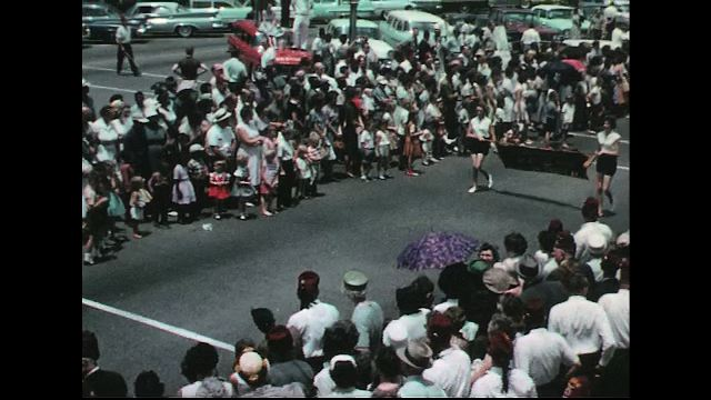 UNITED STATES 1960s: Girls carry banner in parade / Baton twirlers / Band leader with marching band.
