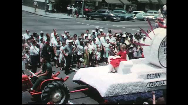 UNITED STATES 1960s: Tractor pulls Carolina Power Company float in parade / Baton twirlers / Majorette leads marching band.