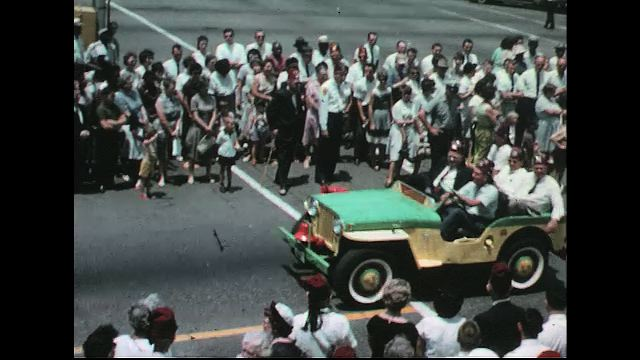 UNITED STATES 1960s: Shriners ride in painted jeep in parade / Baton twirlers lead marching band / Closer view of band / Red Cross ambulance.