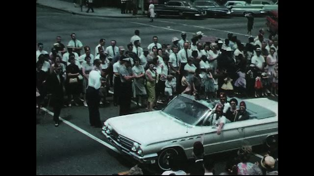 UNITED STATES 1960s: Convertible carries Shriners in parade / Convertible with 'Pitt Co Club' banner / Women wave from back of convertibles.