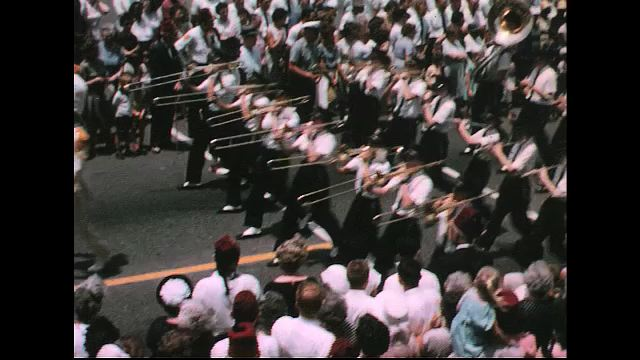UNITED STATES 1960s: Marching band in parade / Pan of marching band / Line of trumpet players, clown dancing