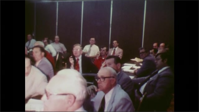 1970s: Men sit in crowded meeting room and talk.