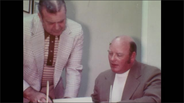 1970s: Men sit in crowded meeting room and talk. Man carries papers to man behind desk. Men talk at office desk. Man gives speech to audience in large meeting hall.