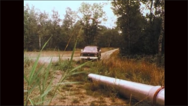 1970s: Truck drives down rural road toward pipe. Truck parks near pipe. Men exit truck.