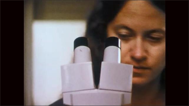 1970s: Eye dropper deposits soil sample on microscope. Woman looks through microscope.