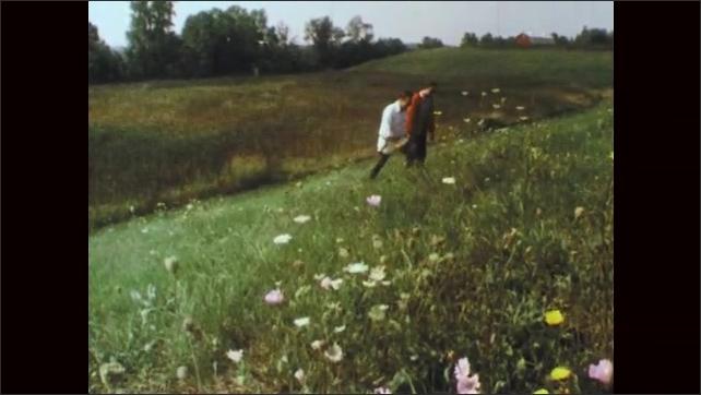 1970s: Men kneel and examine grass in wetlands. Men talk and walk through field. Sunlight streams through tall trees.