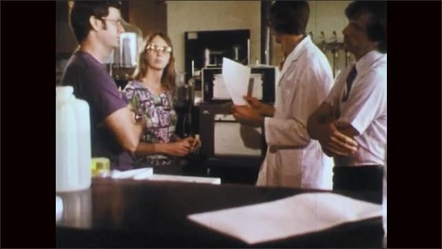 1970s: Man in lab coat speaks to men and woman. Woman speaks.