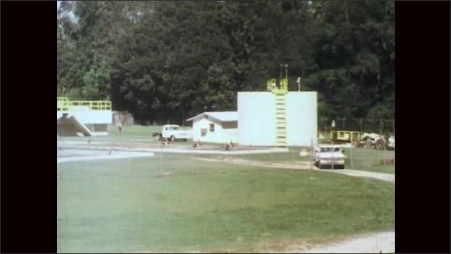 1970s: Farm equipment vehicle crosses railroad tracks in town. Car crosses railroad tracks. Truck drives through field.
