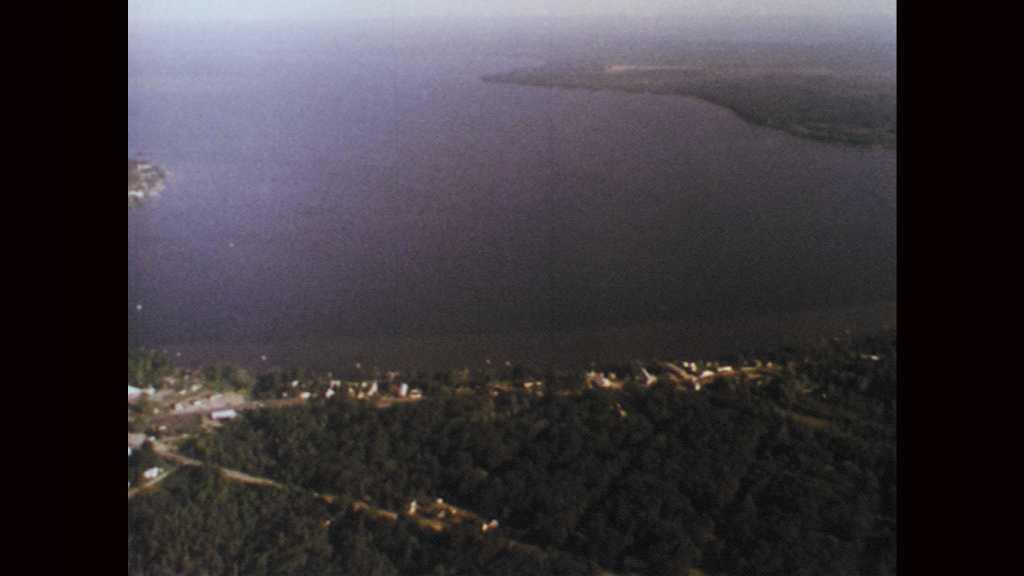 1970s: Aerial view of Houghton Lake. Sail boat skims along surface of lake. Men fish from boat on lake. Children run along dock and climb into motor boat. Man walks along lake shore.