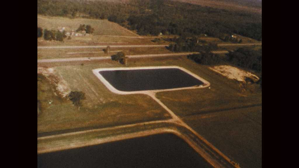 1970s: Aerial view of waste water treatment facility. Aerial view of wetlands marsh. People work at drafting tables in engineering office.