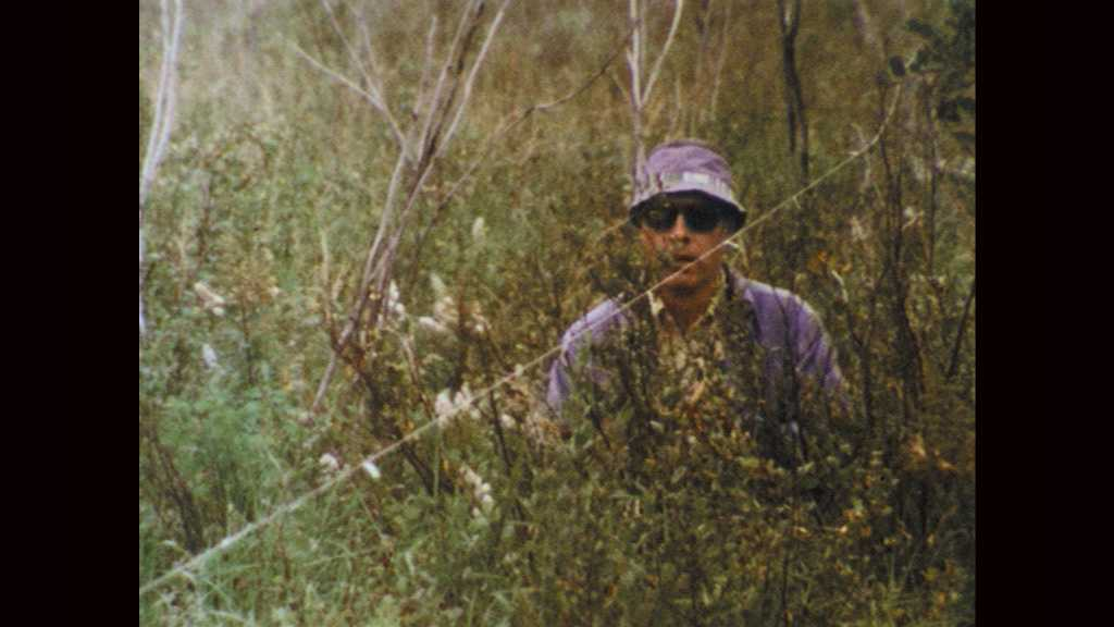 1970s: Man walks through tall grass in wetlands. Woman holds up leaves and speaks. Hands open nozzle on pipe. Water sprays into bag. Man sits on pipe and unloads backpack.