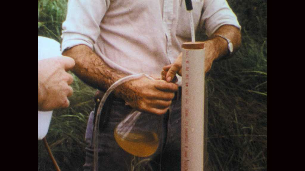 1970s: Men shake water sample in flask. Hands pour water from flask into plastic container. Man walks through cat tails in wetlands. Man removes pocket knife from jacket.