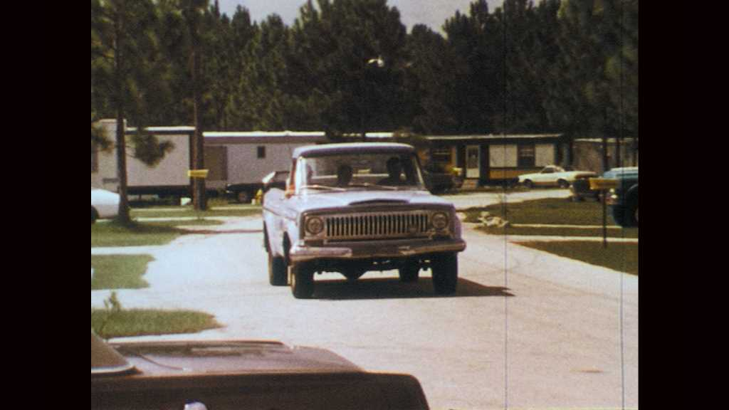 1970s: Truck drives through trailer park and onto dirt road. Man and woman in truck.