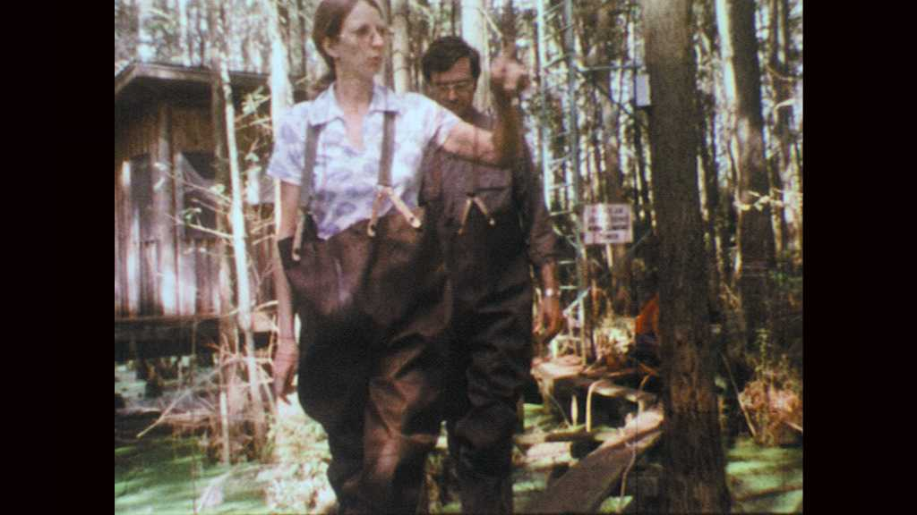 1970s: Woman speaks and points with man standing behind her. Man and woman enter swamp.