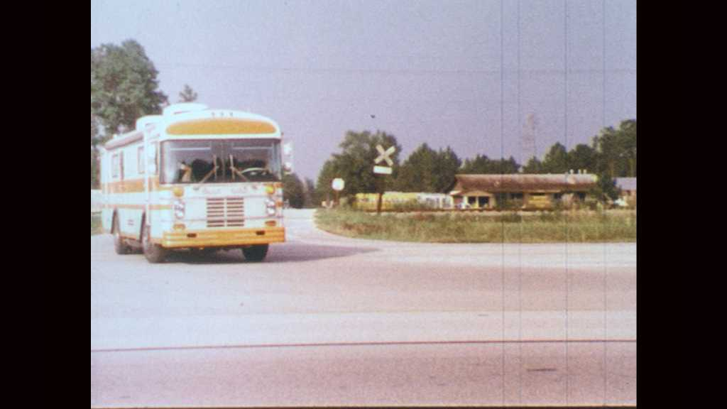 1970s: Recreational vehicle enters highway. RV parked in front of laboratory. Men walk toward lab.