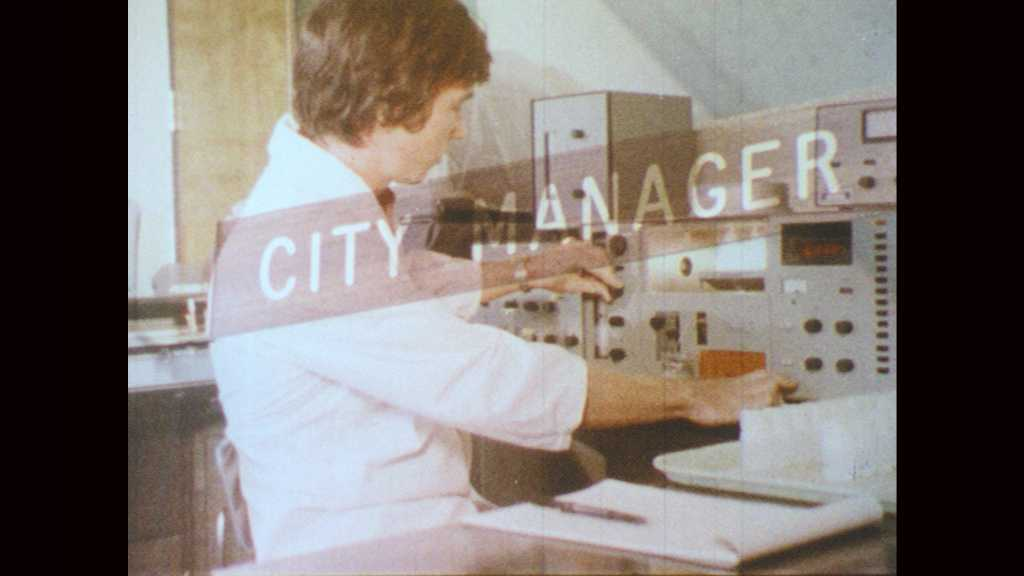 1970s: Sign for city manager's office. Man unfolds paper and spreads it out on desk. Men look at paper.