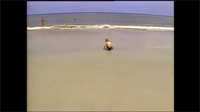 1990s: Pilings in ocean.  Children play on beach.  Teenagers point at book and laugh.