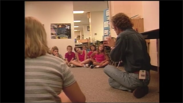 1990s: Man speaks to group of students.  Computerized map of Earth.