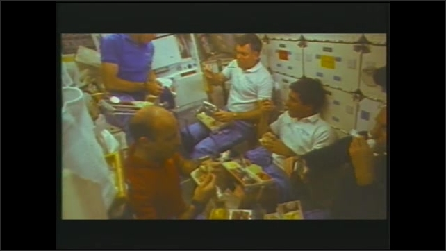 1990s: Spacecraft cabin.  Man uses mouth to grab bits of food from the air.  Woman holds bag.  Men eat together.