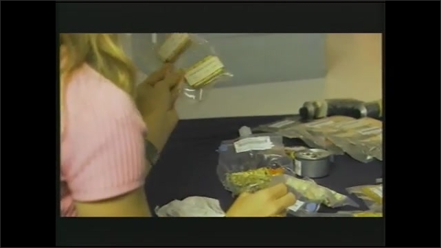 1990s: Astronauts eat in space.  Hand squeezes bag.  Woman holds packets of food and speaks.