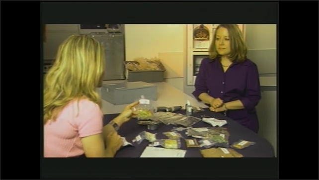 1990s: Astronaut eats from pouch and gives thumbs up.  Women speak.  Table of food pouches.  Woman picks up packet.