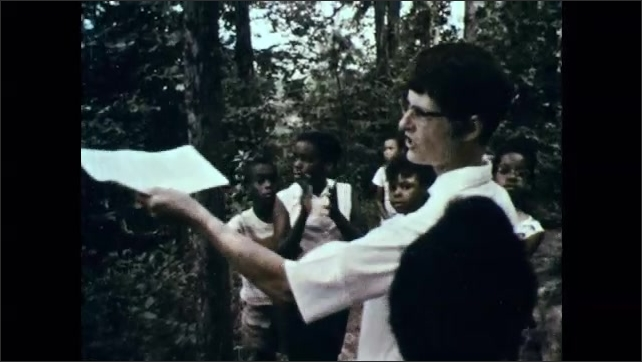 1960s: People walk down path through arboretum. Man holds papers, talks to group, points at plants. Men look through folders of plant samples.