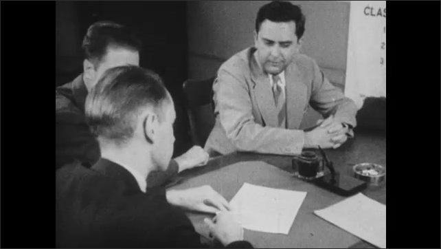 1950s: Men talk and hold meeting at desk in office. Men removes papers from briefcase and passes them to official. Man dips pen in inkwell and signs papers.