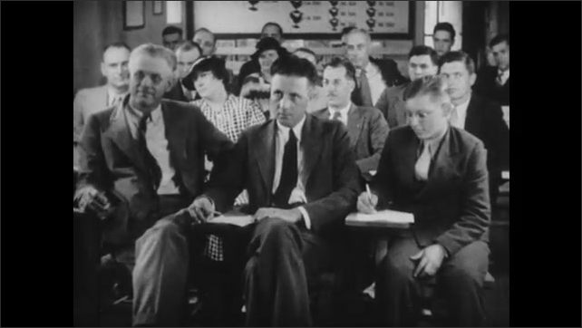 1950s: Men and women sit at desks in classroom and take notes. Man stands at podium in classroom and addresses room.