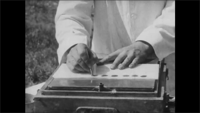 1950s: Hand with wire mixes blood sample and antigen on tablet. Hands tilt tablet with samples near hens on table.