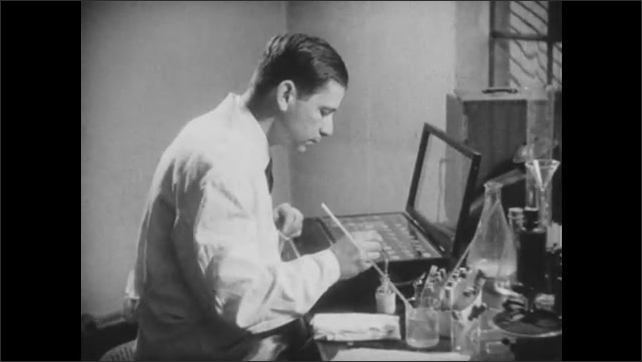 1950s: Scientist places samples of antigen and blood on covered light box with pipette. Man performs antigen testing in laboratory.