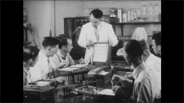 1950s: Instructor observes and speaks to students performing blood tests at laboratory table. Instructor points to examples of blood samples and speaks to students.