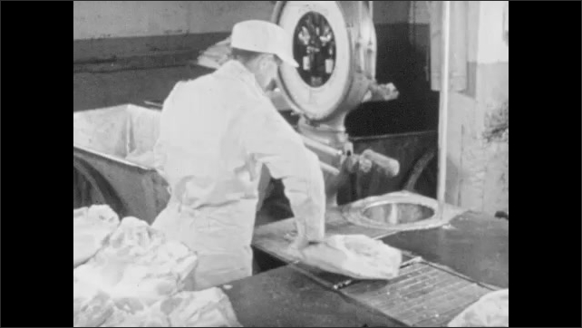 1950s: Butchered pork carcasses pass down conveyor belt, male factory employees slice parts with knives, pass parts through circular saw. Man weighs and inspects ham.