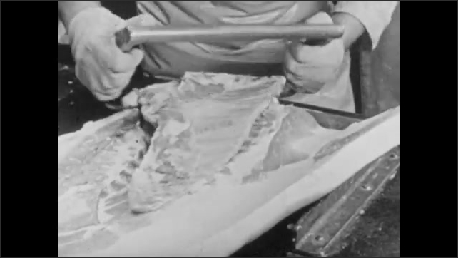 1950s: Man trims meat with knife.  Man cuts meat with saw.