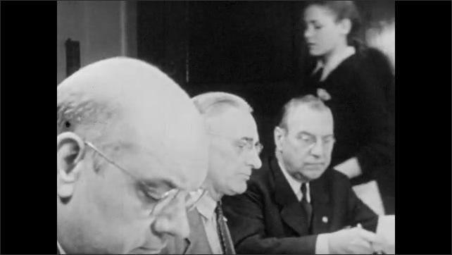 1950s: Men sit at conference table.  Men talk.  Woman passes out papers.  Sheet lists types of meat.