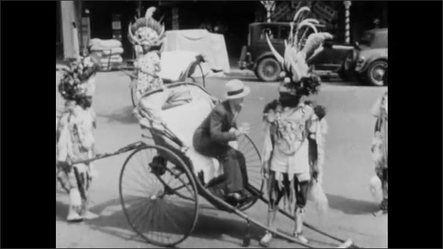 1940s: AFRICA: person in traditional costume in street. Man pulls bike cart and passenger along street. Travel through town.