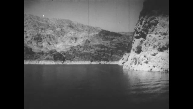 1950s: Water moving  through a dam. The sun behind clouds. Mountain lake. Water rushing through a rocky stream. Lake with a mountain and sun behind clouds.