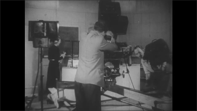 1950s: Cameraman and crew take apart stage and equipment at film set. Man demonstrates Newton's cradle.
