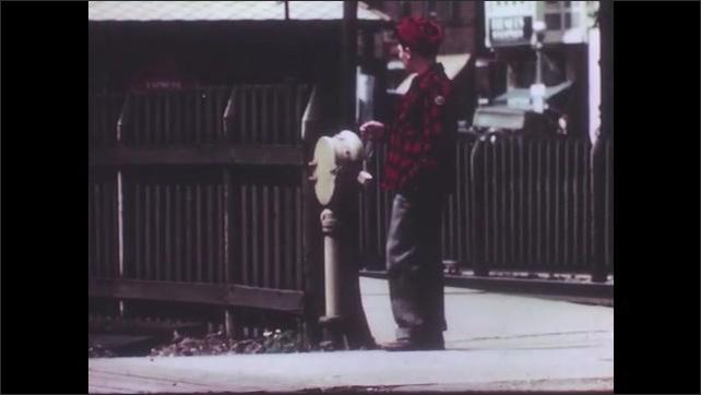 1940s: Train wheels pass by on railroad track. Boy walks away from railroad crossing. Boy walks on the sidewalk.