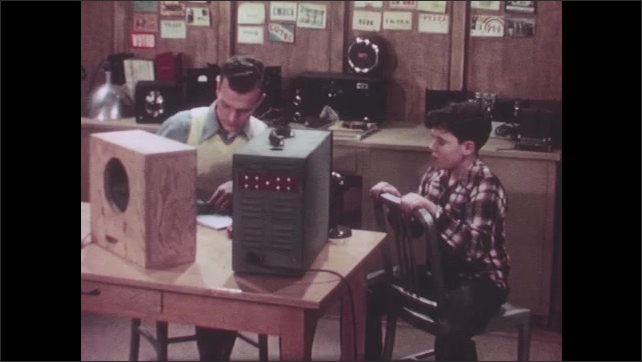 """1940s: Oscilloscope graphic moves and stops. Man talks to boy in an amateur radio studio, man sits and writes on a piece of paper """"amplitude"""" and draws two waves."""