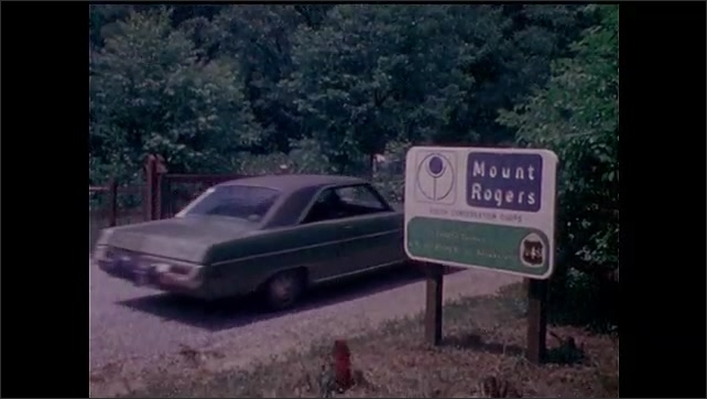 1970s: man and woman pick up and carry log across field. men and women ride horses across rocky creek crossing. car drives past sign for Mount Rogers. people get camping equipment from autos.