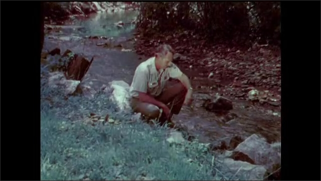 1970s: Man in historical costume jokes with the guide. Woman in historical costume picks up wooden bucket of water and pours it over his head. Man in ranger uniform kneels by a creek and speaks.