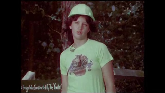 1970s: Young woman in a New York t-shirt and a hardhat walks on a small wooden bridge, faces the camera and speaks. Young man in Conservation Corps uniform and hardhat saws a piece of wood.