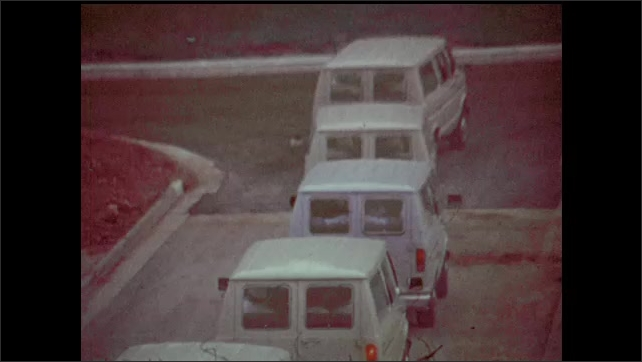1970s: Dog hops into van and sliding door is closed. Convoy of vans drive down the road and turn right. Corp workers in front of waterfall.